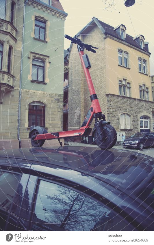 Someone parked an e-scooter on a car e-roller Town Häuers Window Residential area urban intractable bollocks coarse unfug Damage to property prank eMobility