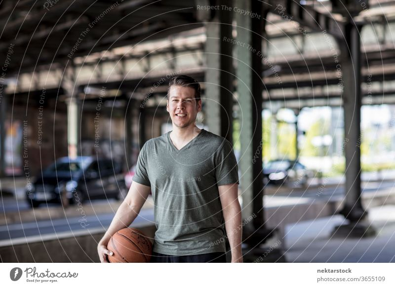 Man With Basketball Standing Under City Bridge adult basketball caucasian urban handsome model one person front facing looking at camera city bridge road