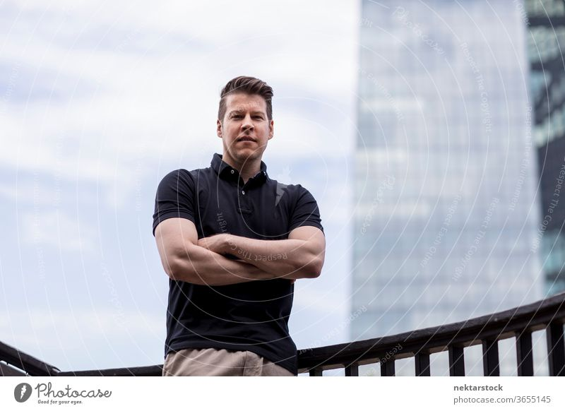 Man with arms folded on sky and building background adult skyscraper caucasian medium shot urban handsome model one person front facing khaki pants balustrade