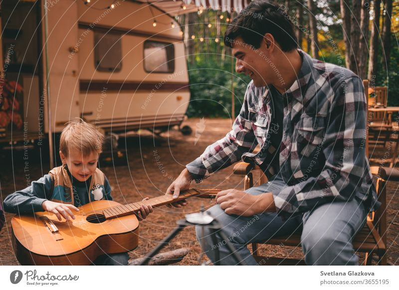 Father teaches son play guitar on camping trip relaxing in the autumn forest. Camper trailer. Fall season outdoors trip family fall nature father mother