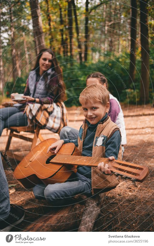 Happy family on a camping trip relaxing in the autumn forest. A boy holds a guitar in his hands fall nature father mother together fun happy people park smiling