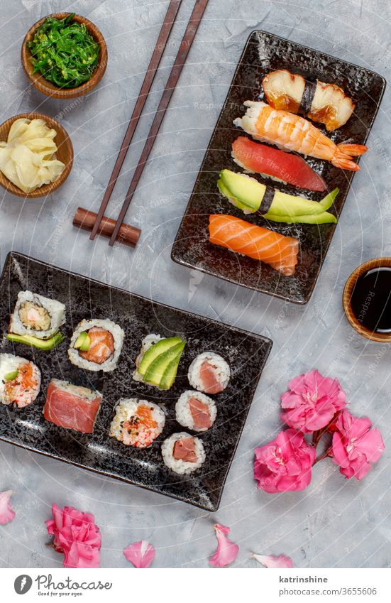 Sushi Set nigiri and sushi rolls on rectangular plates ready to eat eating Sashimi Rolls Maki sushi bar dinning Japanese Culture Seafood chopsticks grey flowers