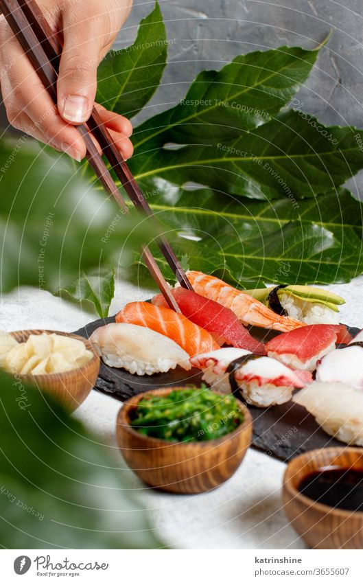 Close up of hand taking suchi with chopsticks from a plate sushi ready to eat eating Sashimi Rolls sushi bar leaf copy space dinning Japanese Culture Seafood