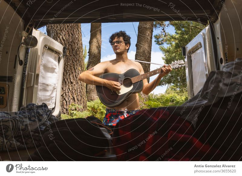 Guy playing adventure guitar in the forest (camping) seen from the inside of a minivan Relaxation Guitar recreation tourism journey trip outside young smile