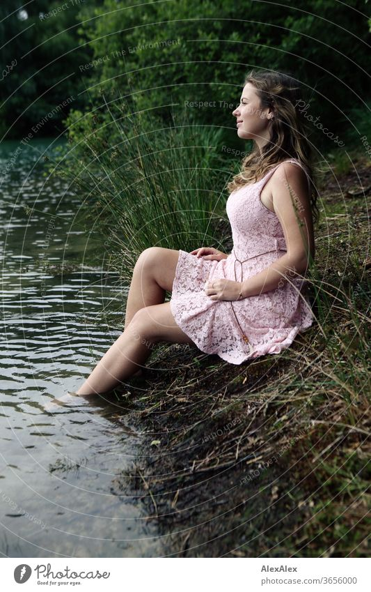 Young woman in a pink summer dress sitting in a clearing with her feet in the forest lake Woman girl Forest Grass plants foliage green Nature Dress Barefoot