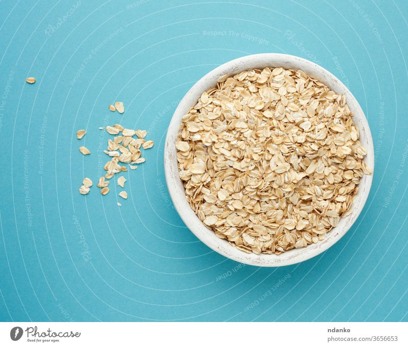raw oatmeal in a white wooden bowl on a blue background diet organic ingredient dry food breakfast healthy natural cereal vegetarian nutrition closeup grain