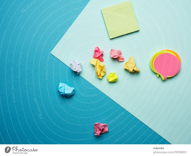 multicolored blank paper stickers of different colors on a blue background stationery sticky template yellow adhesive announcement business closeup colorful