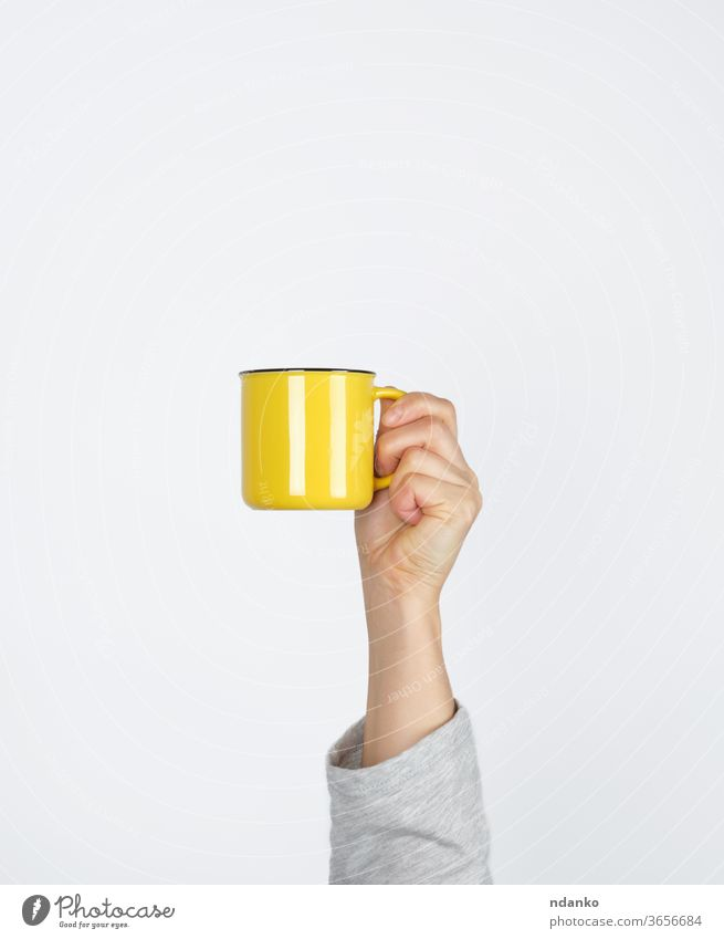 yellow ceramic cup in a female hand on a white background coffee coffee break container design drink espresso finger food hold hot kitchen left lunch mug one