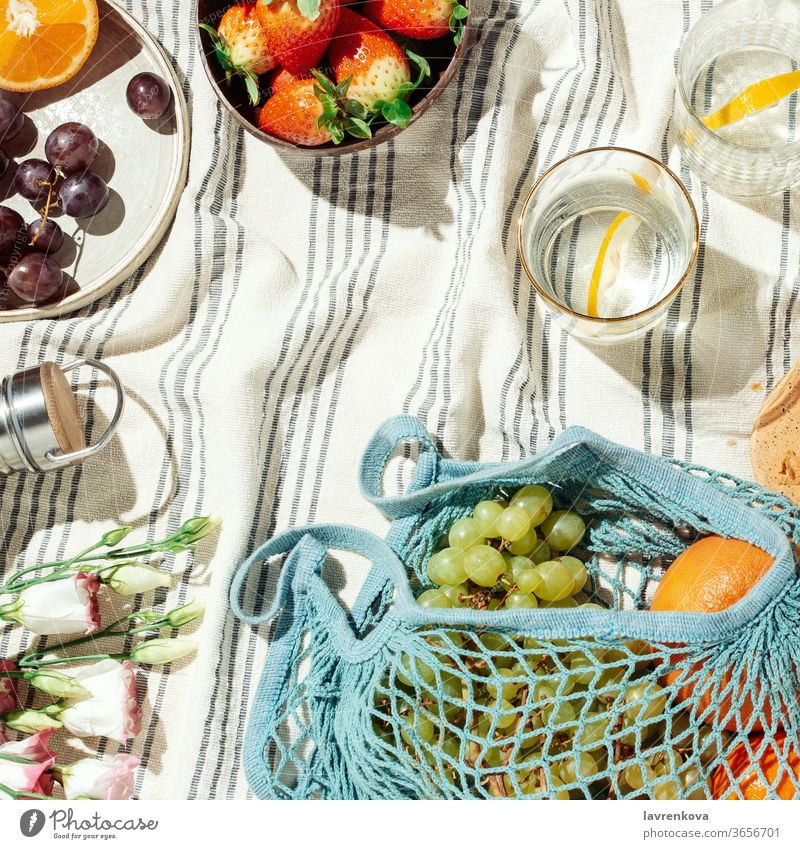 Summer picnic flatlay, fruits, berries and lemon water on striped cotton blanket summer food eating diet fresh glasses citrus seasonal grapes string bag