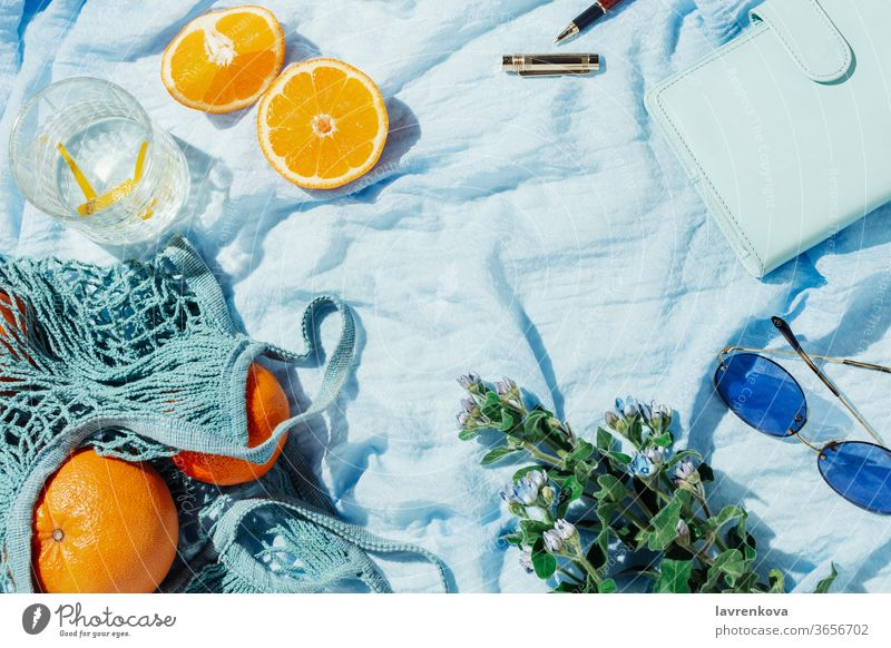 Summer picnic flatlay of fruits, flowers and lemon water on a blue blanket summer glasses citrus seasonal fresh string bag zero waste bouquet spring notebook