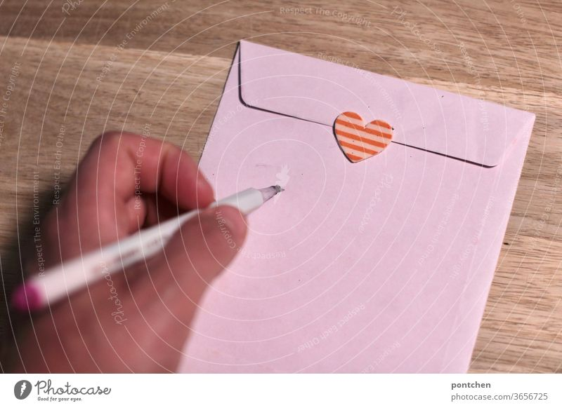 Left-handed. One hand holds a pen in writing position. An envelope closed with a heart sticker is addressed. Love letter. Mail enveloped in a letter