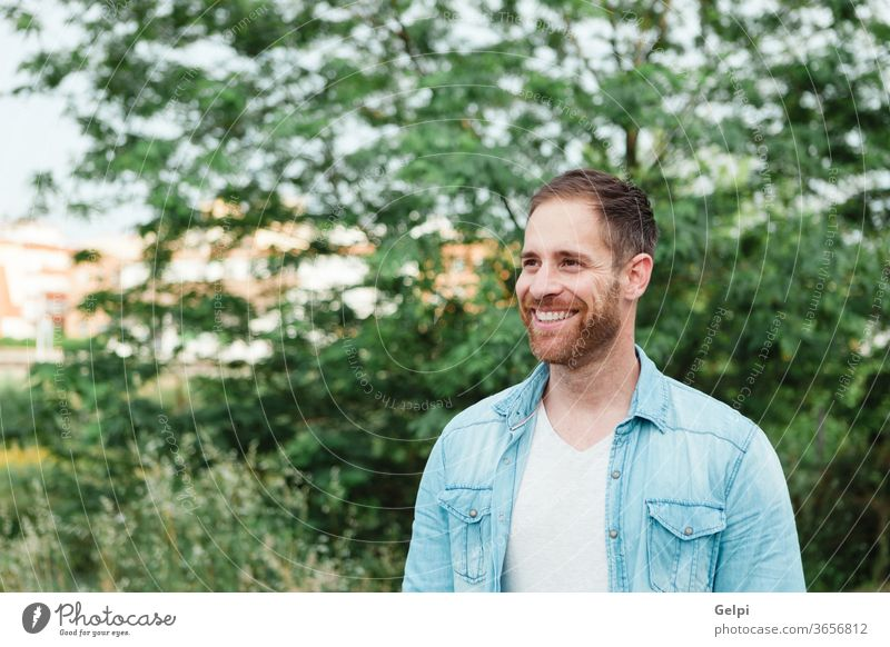 Portrait of a casual men in a park male young handsome man model guy beard fashion portrait denim attractive people adult person confident style enjoy shirt