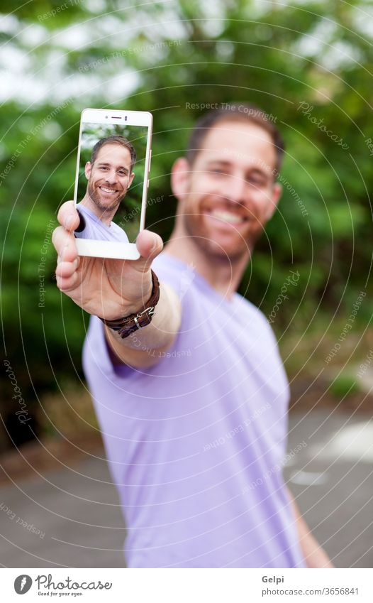 Casual guy in a park taking a photo person man mobile phone lifestyle young portrait selfie technology happy modern image male handsome people smartphone