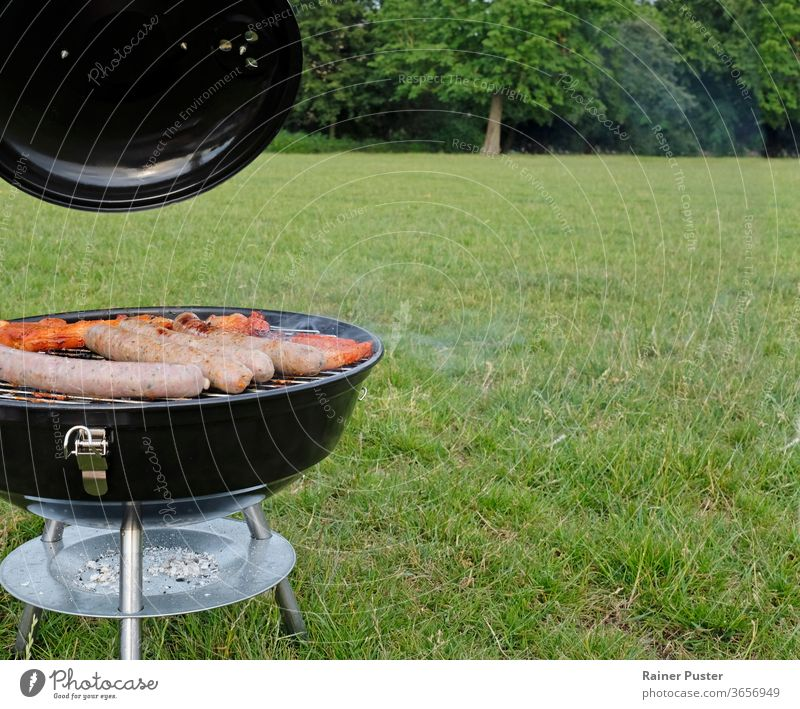 Barbecue season: BBQ grill with steaks and sausages in the park background barbecue barbeque bbq beef charcoal cook cooking delicious fire food grass grilled