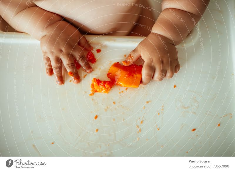Close up baby eating fruit hands Hand body part Baby babyhood Eating Fruit Papaya Healthy Eating Interior shot Colour photo Nutrition Red Fresh Close-up Sweet
