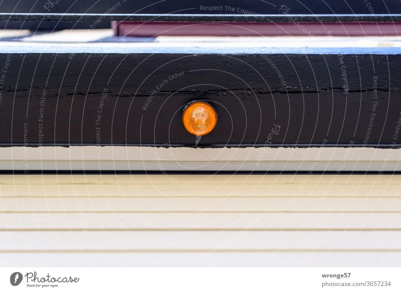 Orange signal lamp on a bar above a closed automatic garage door Garage door Automatic Electrical appliance Deserted Exterior shot Colour photo Day