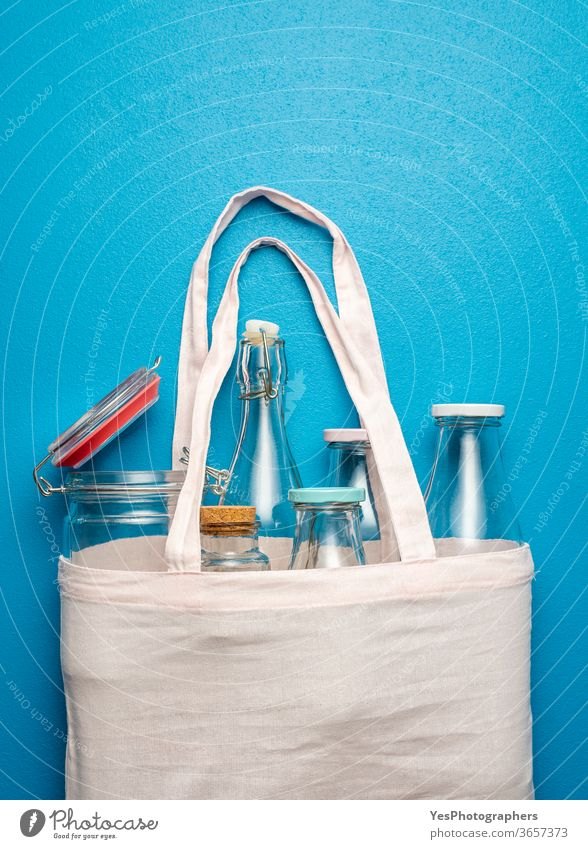 Nonplastic containers for storage and shopping. Cotton bag with glass bottles and jars above view background blank blue bulk shopping buy clean concept