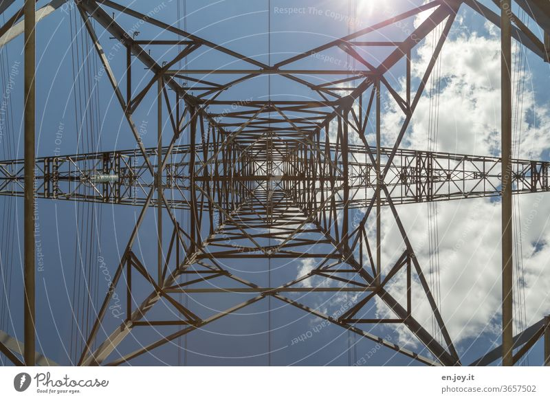 Power pole from below with blue sky, sunlight and a cloud in times of climate change Electricity pylon stream electricity Energy Energy industry