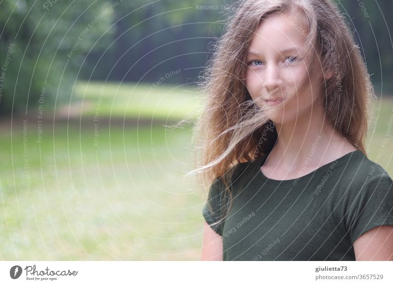 Portrait of a smiling girl with wind in her hair in the park portrait Half-profile motion blur Shadow Light Day Exterior shot Colour photo Puberty Emotions