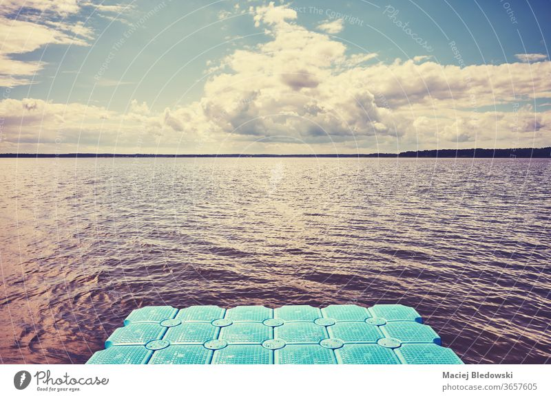 Floating plastic pier on water. floating deck lake sea nature instagram effect relax toned filtered cloud sky cloudscape weather sunlight photo sunny nobody
