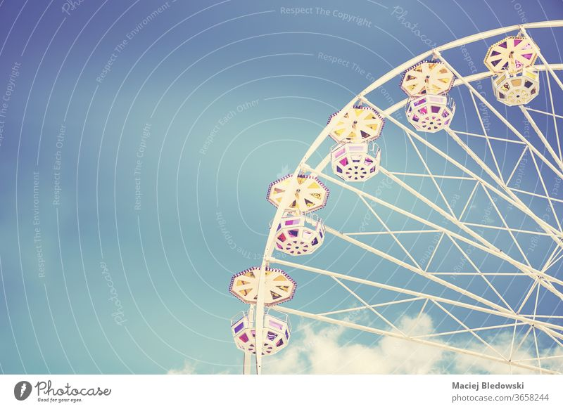 Retro toned picture of a Ferris wheel on a sunny day. ferris amusement fun sky ride childhood retro instagram effect entertainment summer leisure joy circle