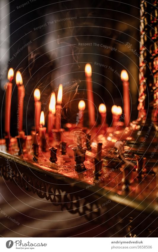 long lighted candles group in orthodox church. candles background. selective focus dark religion catholic wax christian symbol religious peace holiday yellow