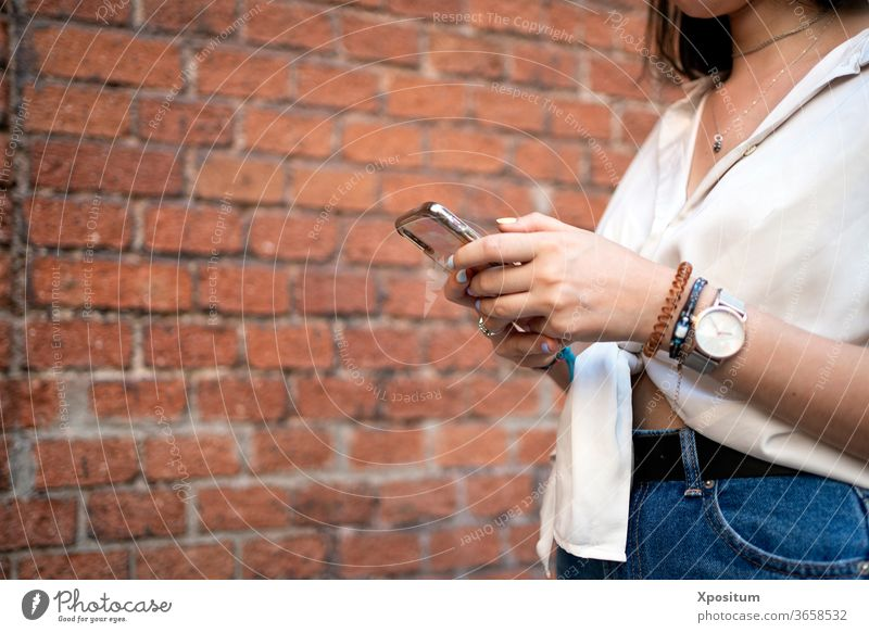 Side view of a close up of an unrecognizable woman using her smartphone alone attractive beautiful beauty cellphone city communication commute device female