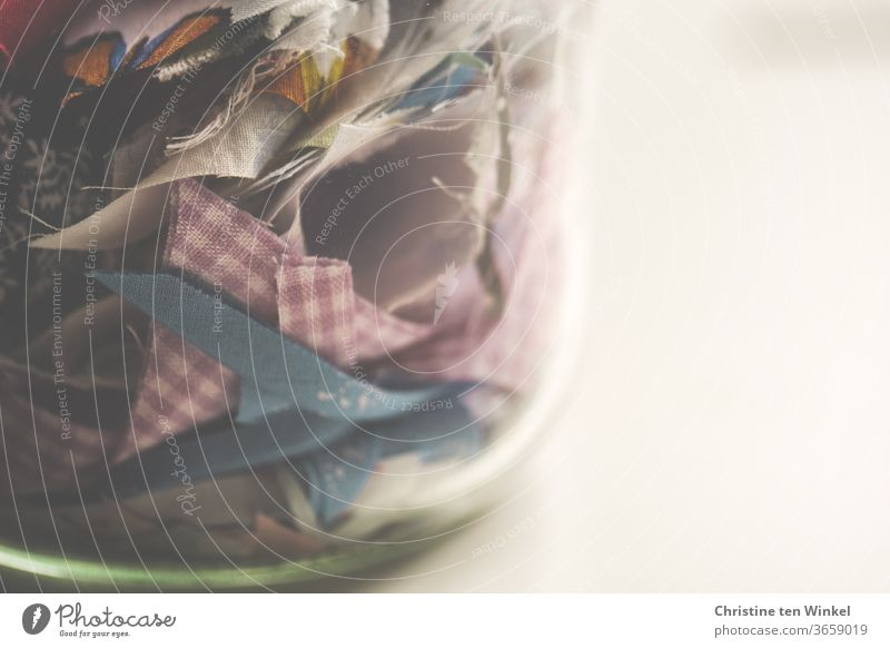 Coloured fabric remnants in a thick-walled glass. Close-up with space for text fabric snippets Cloth Snippets Glass Preserving jar Keep lift Sewing Handcrafts