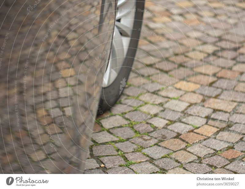 Cobblestone pavement with reflection in a car door. You can also see a part of the front wheel Cobblestones natural stone pavement Car door Car tire Front wheel