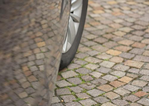 Cobblestone pavement with reflection in the paint of a car door. You can also see a part of the front wheel Car door Reflection Car paint Cobblestones