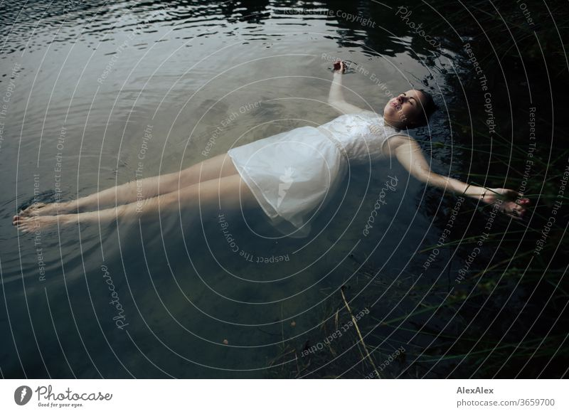 Close portrait of a young woman in a white dress lying in a lake Curly Purity Beautiful weather Trip Expectation Sunlight Joy Close-up Feminine Day Full-length