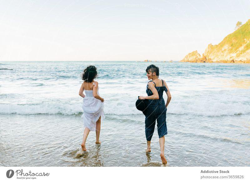Happy women running on foamy sea near shore beach vacation friend tourism fun barefoot entertain girlfriend harmony ocean together mount partner pleasure hat