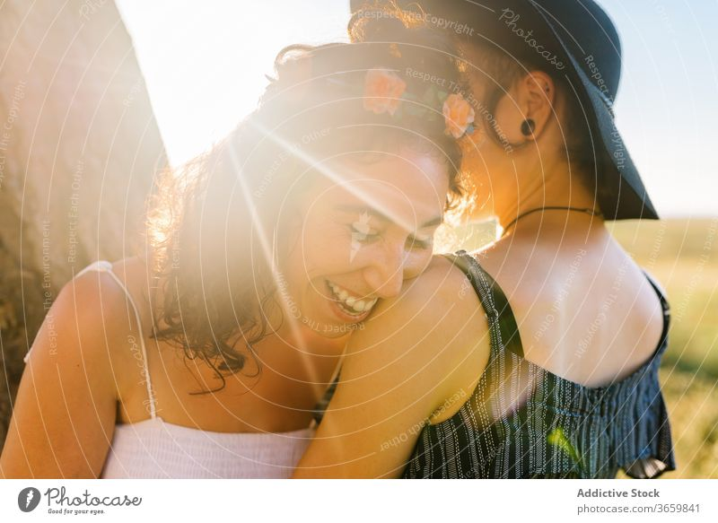 Delighted lesbian couple cuddling during sundown homosexual hug sunset women summer together relationship stroll girlfriend affection embrace close date lgbt