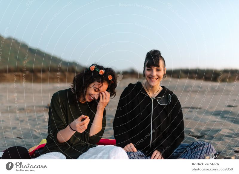 Cheerful girlfriends spending time together on sandy beach in daylight relax tourism couple spend time laugh eyes closed harmony sensual love satisfied positive