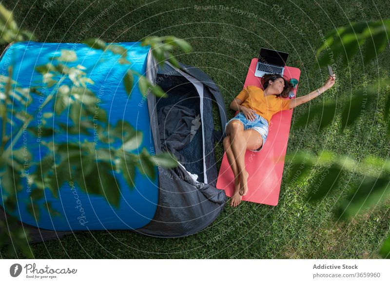 Happy woman taking selfie near camping tent smartphone happy summer rest enjoy gadget cheerful smile mobile lying modern nature relax meadow grass young female