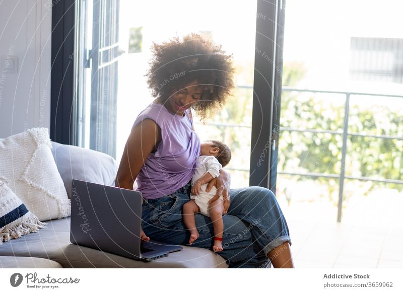 Busy ethnic mother with infant using laptop baby breastfeed work freelance woman sofa busy newborn project female african american black netbook home gadget