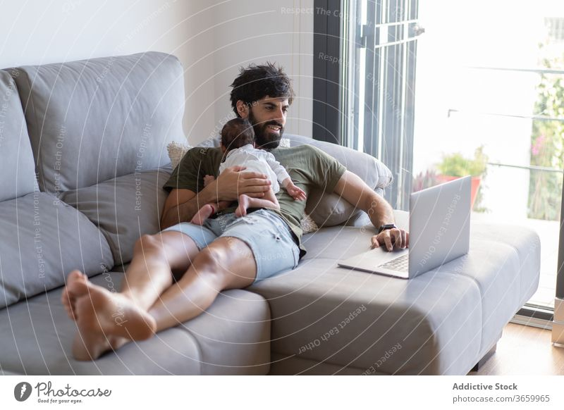 Busy father with infant using laptop baby work freelance sofa busy newborn project male fatherhood netbook home gadget remote browsing internet surfing online