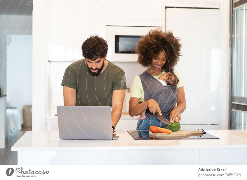 Multiracial family together in kitchen counter parent cook work father mother baby multiethnic multiracial diverse african american black arab laptop love child