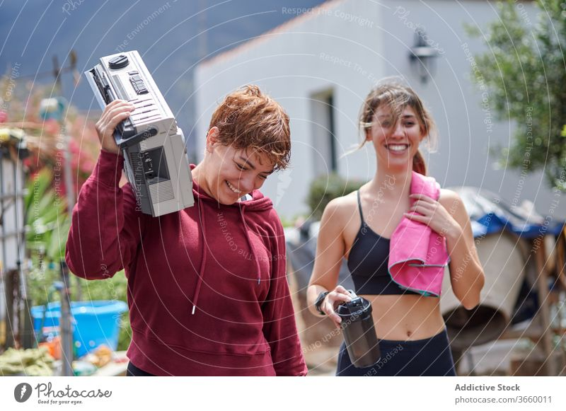 Excited sportswomen with boombox walking in backyard rest country happy excited listen fitness sportswear relax workout together athlete joy strong toothy smile
