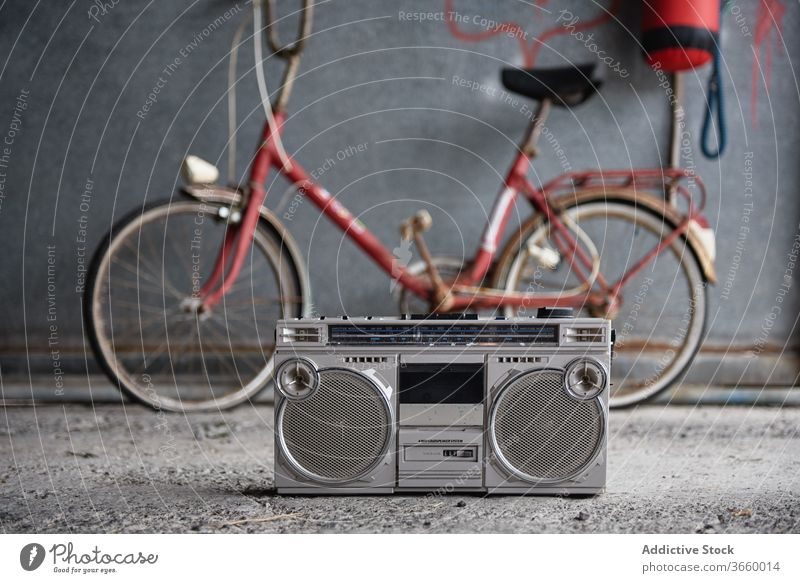 Retro boombox against bicycle in garage tape player single cassette old fashioned retro concrete floor obsolete portable nostalgia grunge gray shabby wall