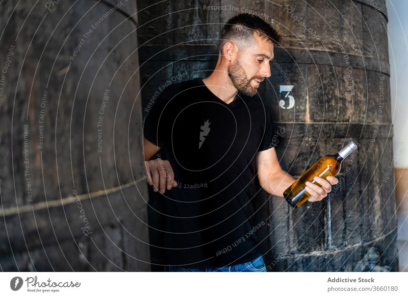 Winemaker with bottle of wine near huge wooden barrel winemaker check positive winery factory viticulture winemaking production industry contemporary
