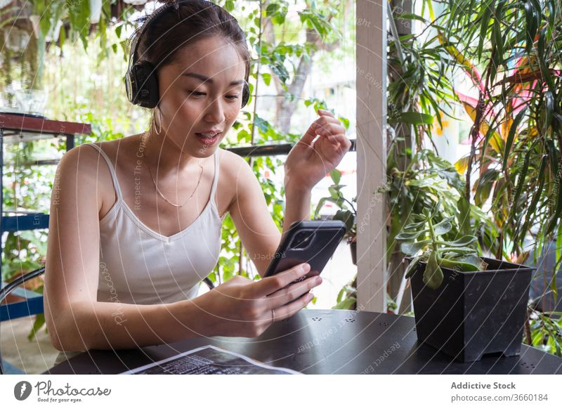 Asian woman watching video on smartphone funny headphones enjoy entertain using smile asian ethnic summer gadget young device mobile cheerful connection rest
