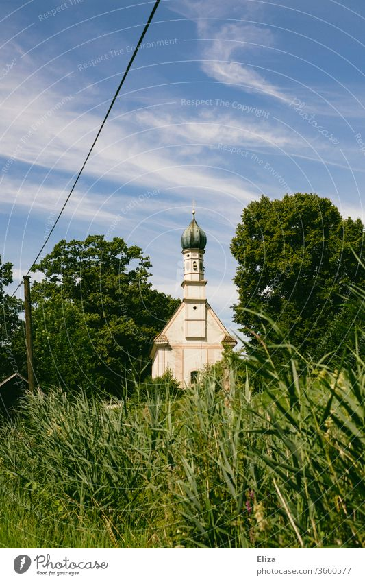Church in the green, surrounded by trees and blue sky. Nature Green Sky Church spire Religion and faith Building Christianity Manmade structures Meadow Grass