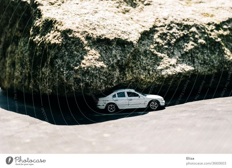 A car under the rock Rock Vehicle Sun Shadow jammed Dangerous Sparse White Threat Emergency situation Toy car Car Breakdown Parking Parking lot