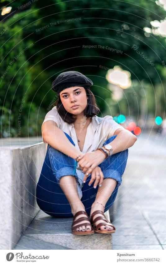 Young woman seating and looking at camera street female portrait city caucasian beautiful young people person fashion girl attractive outdoor beauty urban