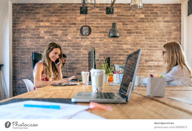People working in a coworking office businesswoman coworkers teamwork phone communication talking people job professional young workplace industrial decor style