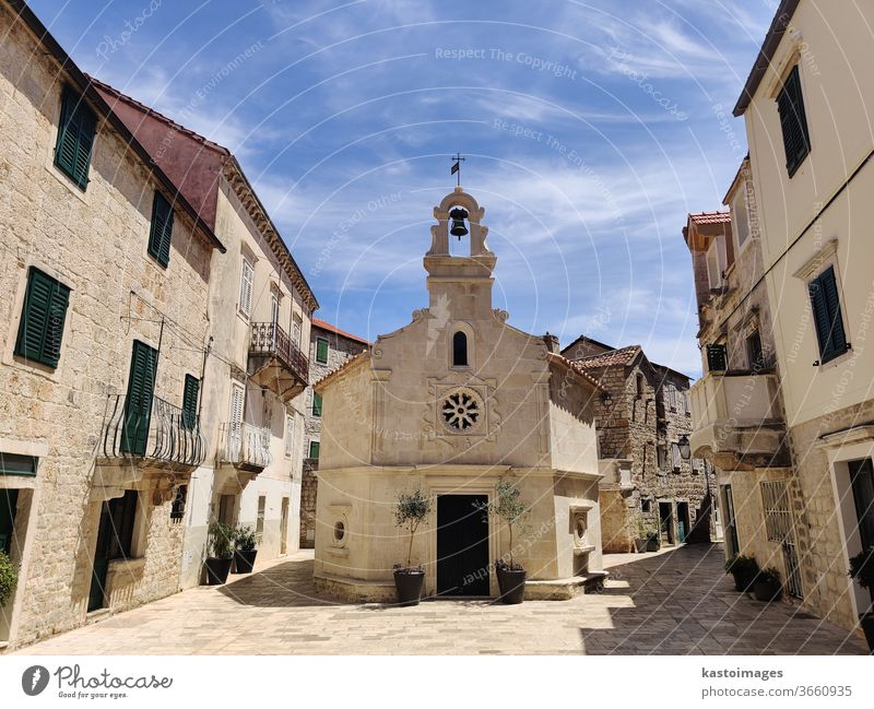 Picturesque old stone made little church in the middle of traditional town square in Jelsa, Hvar island, Croatia. Island Village Exterior shot Fishing village