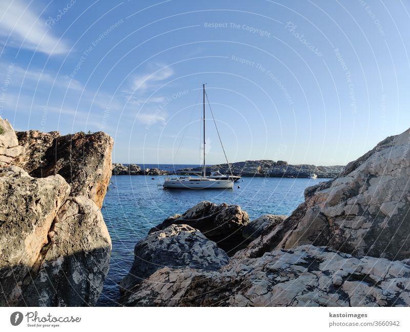 Sailboat mooring in calm bay surrounded by rocks sailing boat Sailing Water vacation travel Freedom Summer Sailing ship Vacation & Travel Ocean Adventure sea