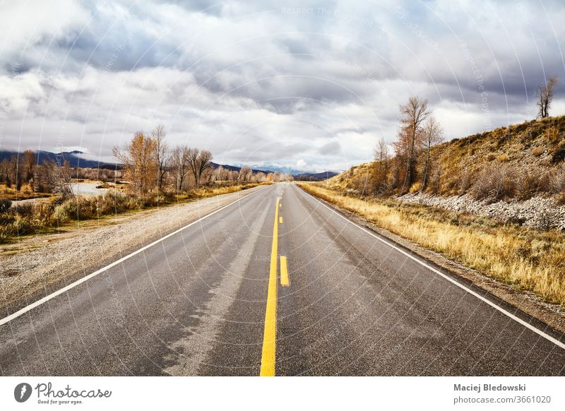 Scenic road in Grand Teton National Park, USA. travel trip journey landscape nature Wyoming national park autumn season clouds mountain hill sky valley scenic