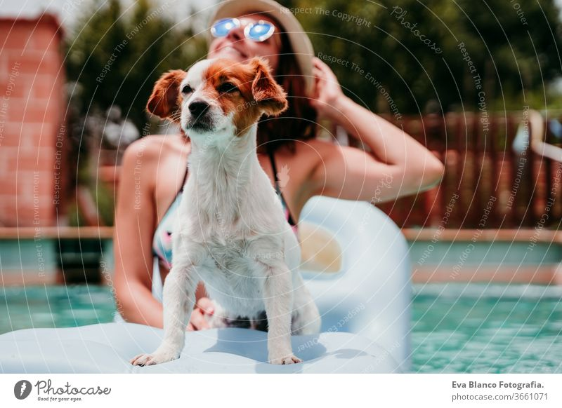 happy woman and dog in a pool having fun. sitting on inflatable. Summer time swimming pool blue water summer time love jack russell hat young together